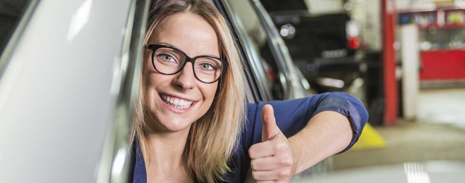 Happy Girl showing thumbs up in auto mechanic shop
